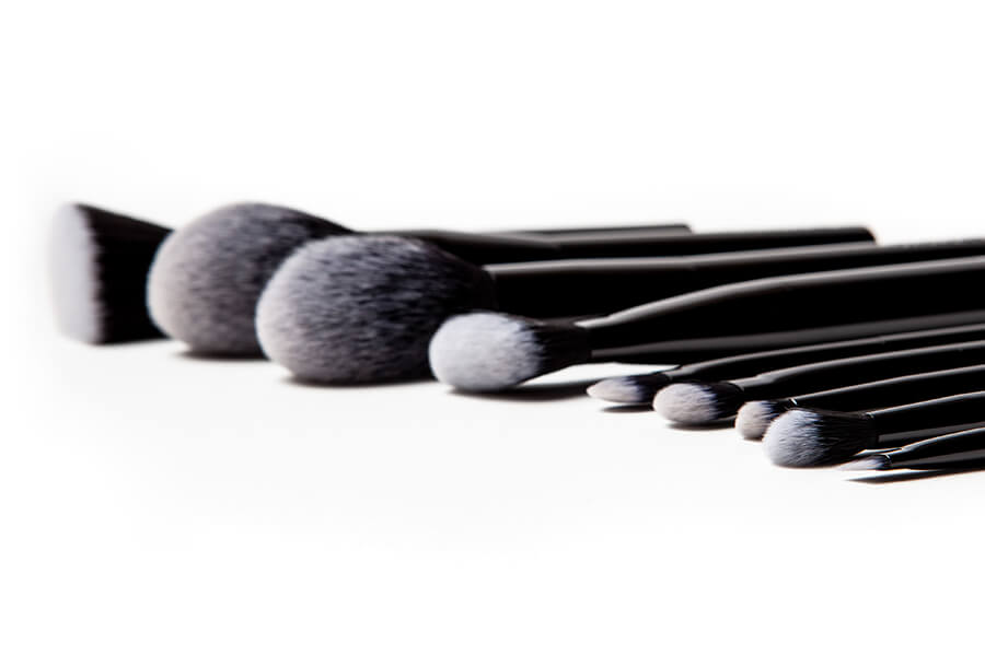 Crunchi brush being dipped in a canister of Crunchi eyeshadow